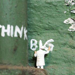 """Un petit homme écrivant """"Think Big"""""""