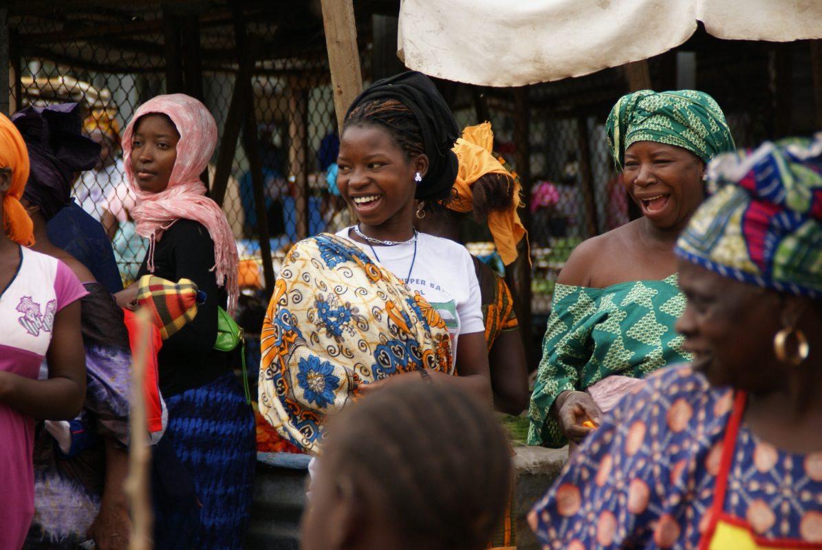 Femmes vêtues de pagnes et habits colorés dans un marché